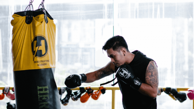 A boxer with tattoos punching a heavy bag with boxing gloves on.