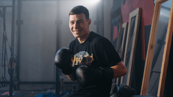 A man smiling at the camera with venum boxing gloves on