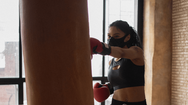 A woman punching a heavy bag with boxing gloves on
