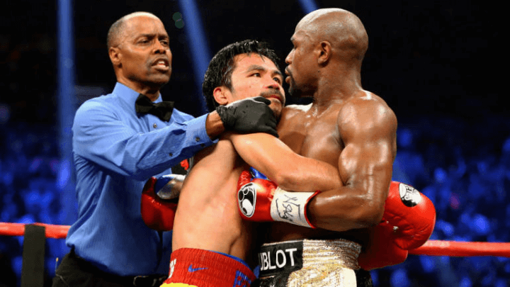 Floyd Mayweather and Manny Pacquiao clinching and being seperated by a referee