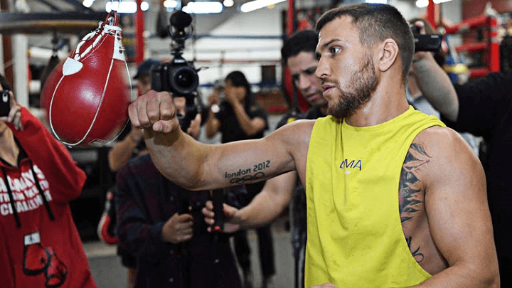 Lomachenko hitting the speed bag with press in the background