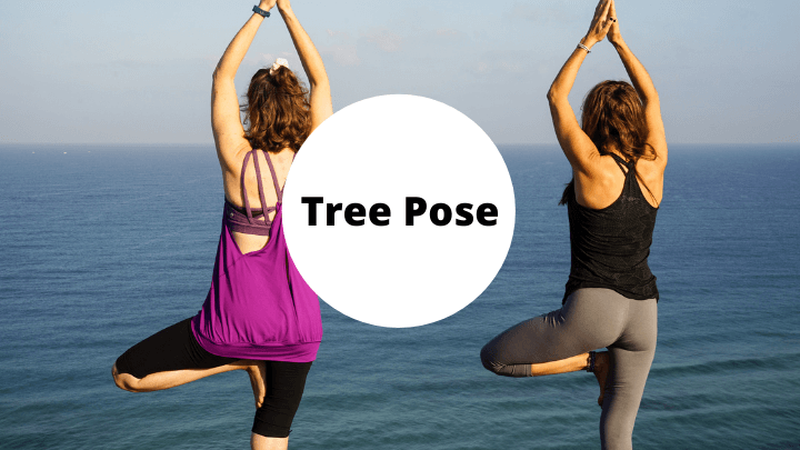 Two women doing tree pose by the ocean