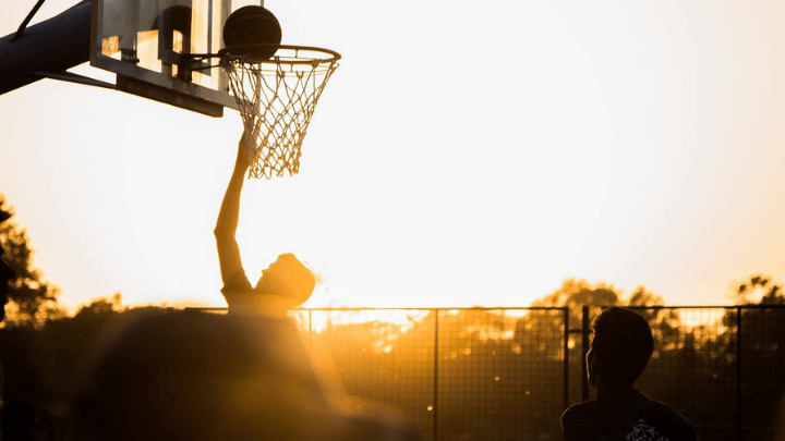 Two basketball players playing on an outdoor court with the sun going down.
